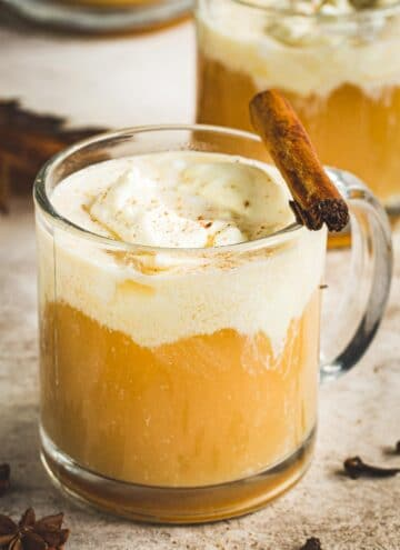 Caramel Bourbon Apple Cider Cocktail in a glass coffee mug topped with whipped cream and a cinnamon stick.
