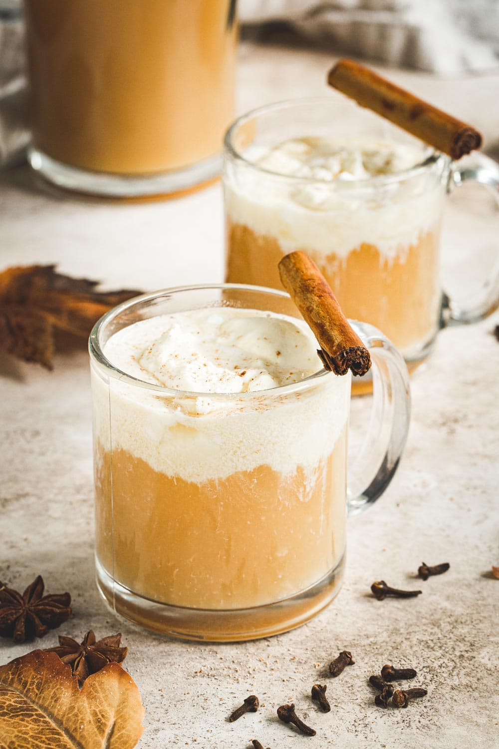 Two glasses of caramel bourbon apple cider cocktail with a cinnamon stick on top.