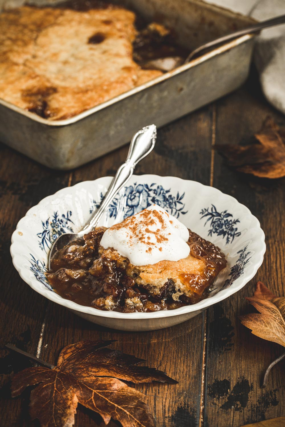Pecan pie cobbler topped with whipped cream and cinnamon in a dessert bowl with a silver spoon.