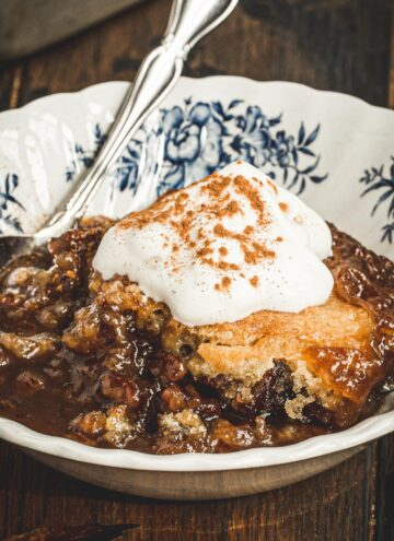 Pecan pie cobbler in a dessert dish with whipped cream on top.