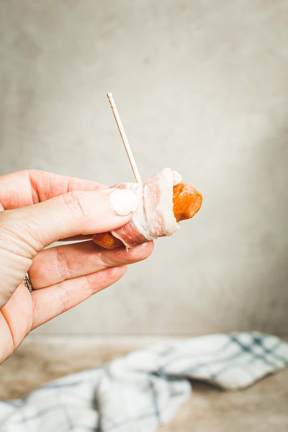 Hand holding a bacon wrapped little smokie.