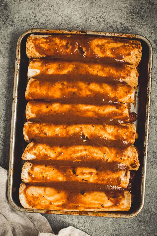 Enchiladas covered in enchilada sauce on a rimmed baking sheet.