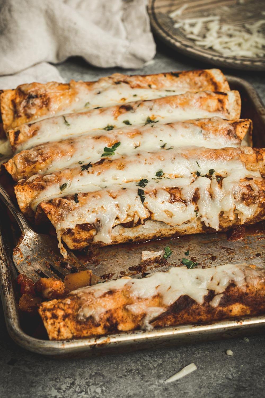 Butternut squash enchiladas on a rimmed baking sheet with metal spatula.