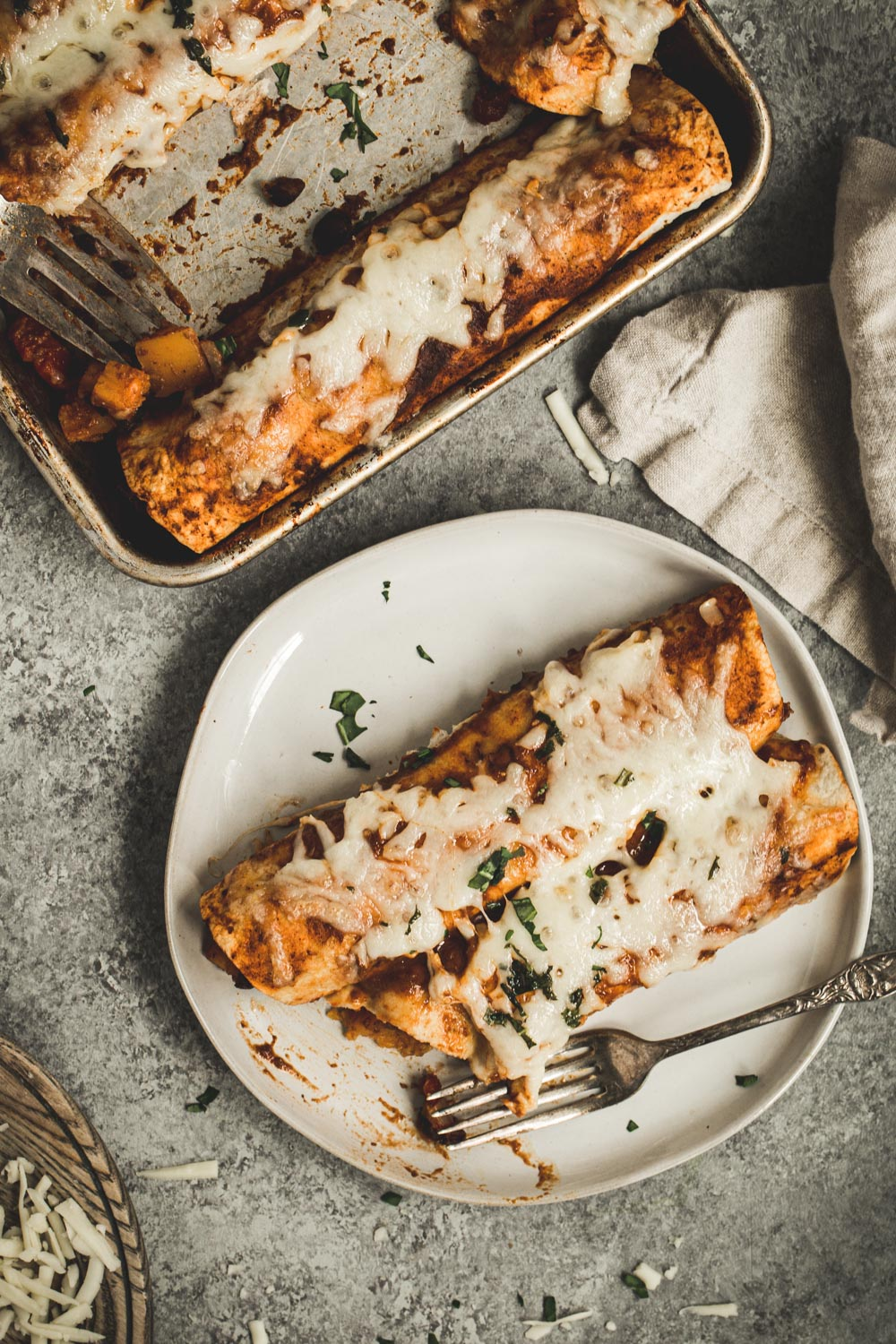 Two enchiladas on a white plate with a silver fork.