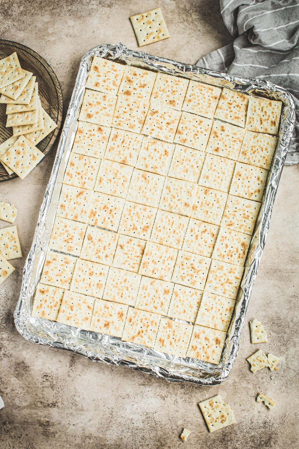 Saltines laid out on a foil-lined baking sheet.