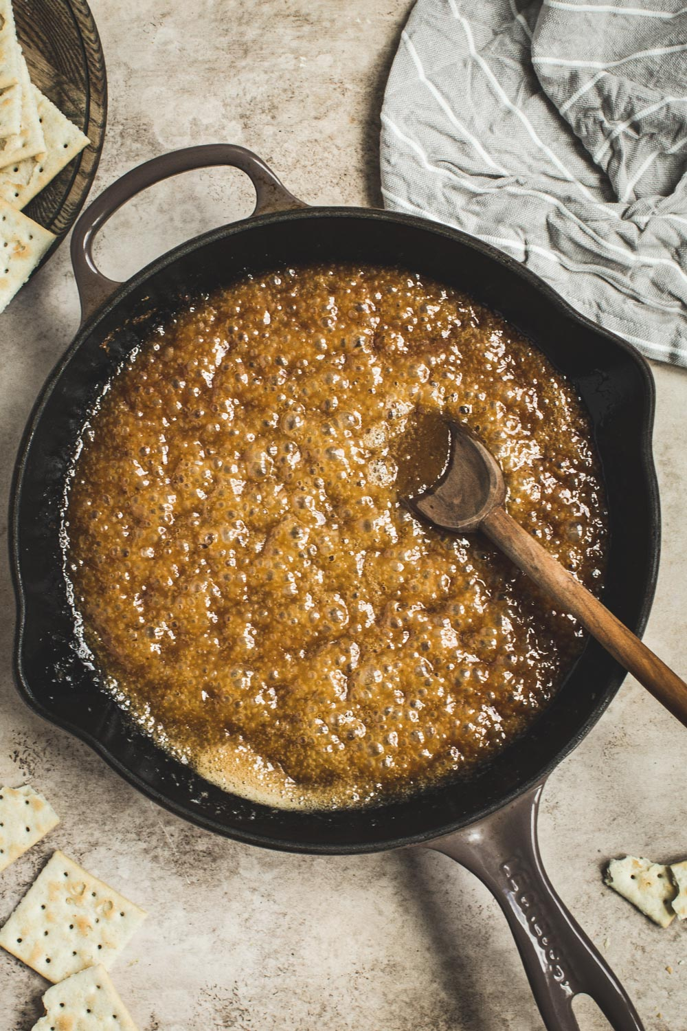 Butter and brown sugar mixture in an iron skillet with a wooden spoon.
