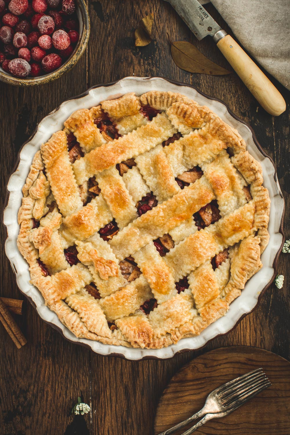 Apple and Cranberry Pie with a lattice crust in a white pie dish sitting on a wooden table.