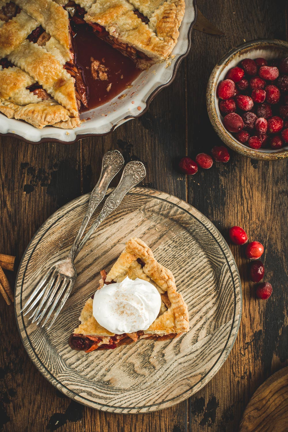 Slice of apple and cranberry pie topped with whipped cream on a wooden plate.