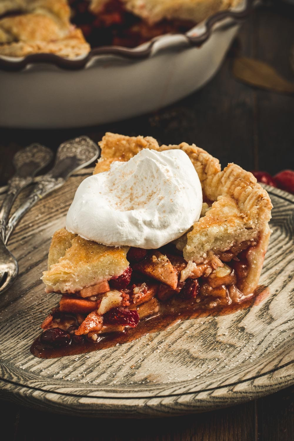 Slice of apple and cranberry pie topped with whipped cream and sitting on a wooden plate.