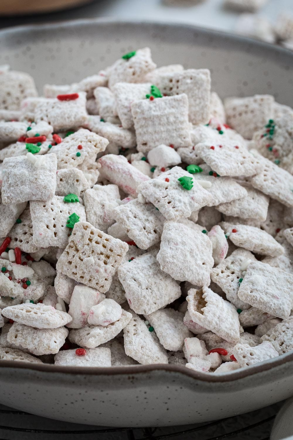 Close up of Christmas muddy buddies covered in powdered sugar and topped with sprinkles.
