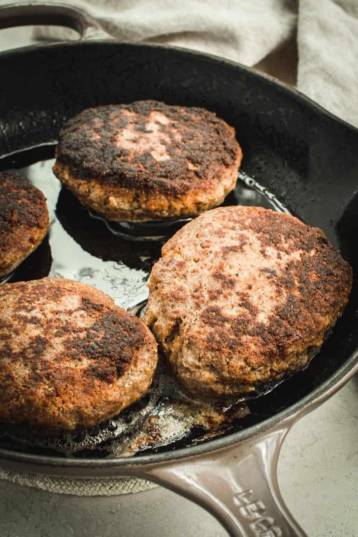 Cooked salisbury steak patties in an iron skillet.