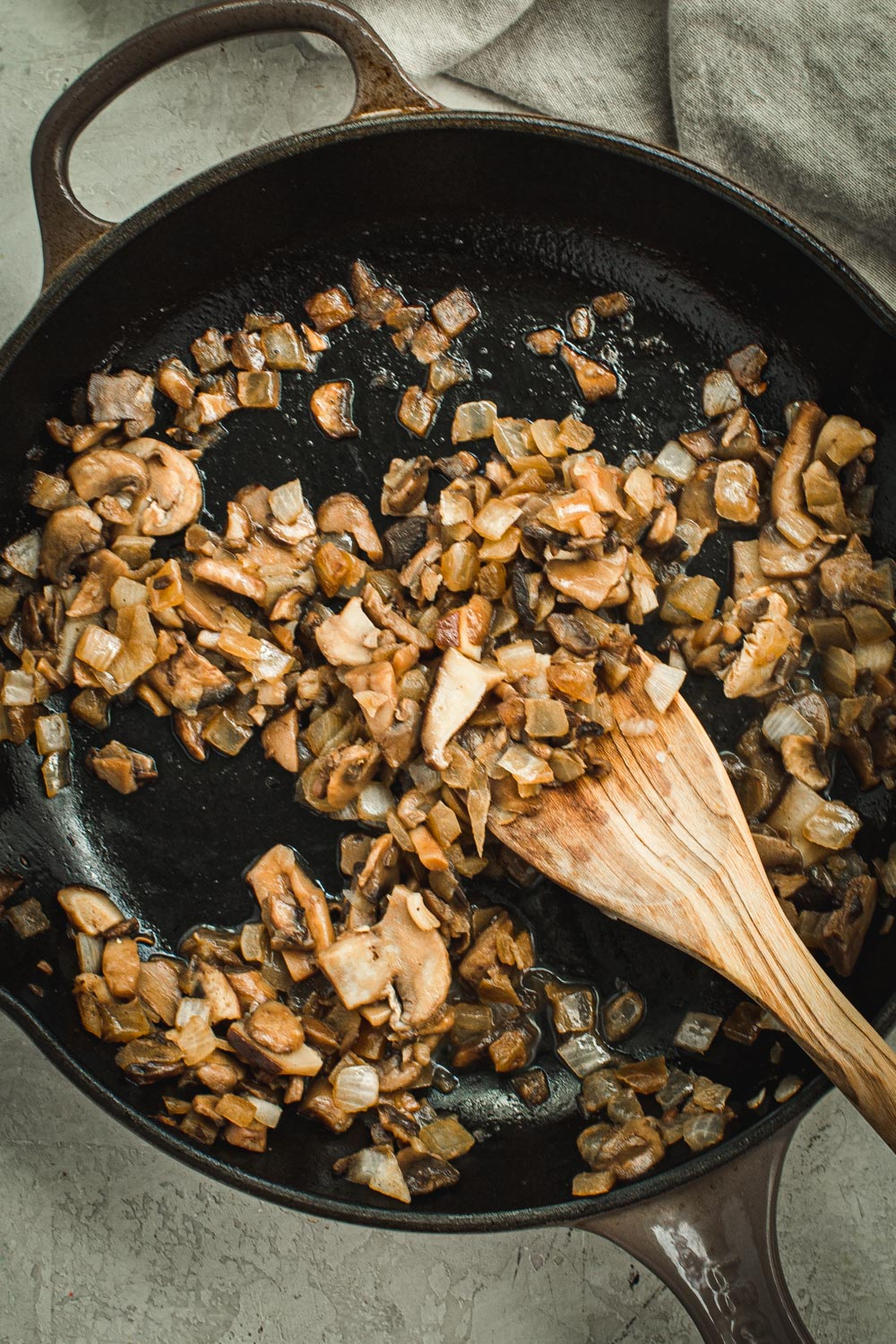 Mushrooms in iron skillet with wooden spatula.