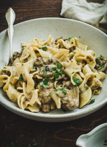 Ground beef stroganoff over egg noodles in a gray bowl.