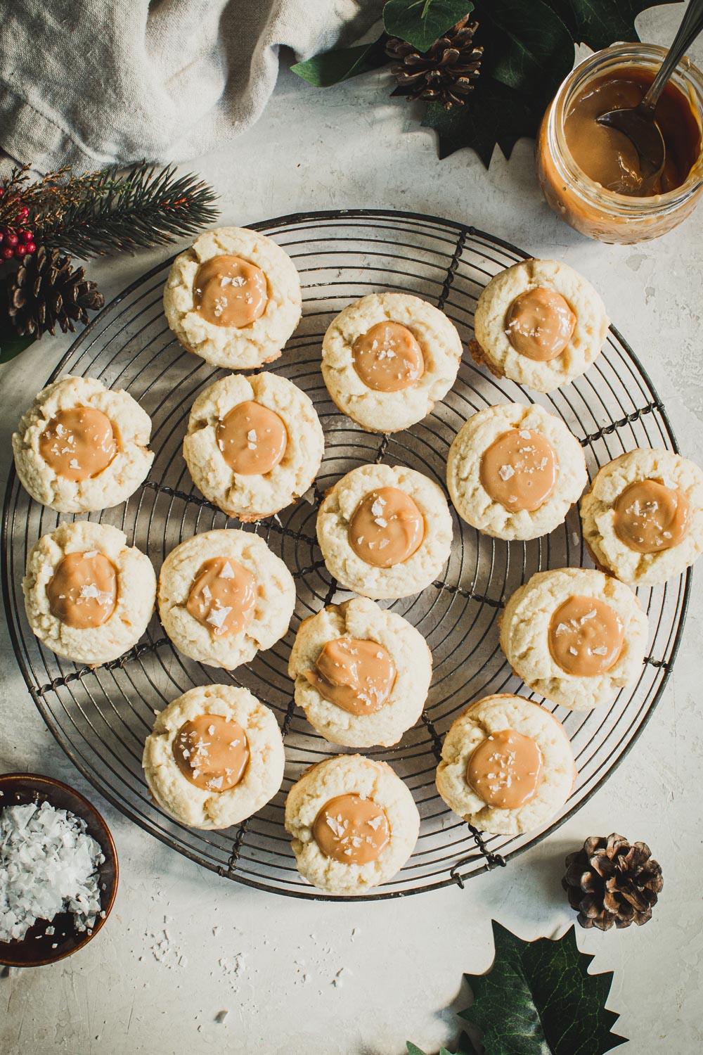 Dulce de Leche thumbprint cookies on a round wire rack with Christmas holly surrounding.