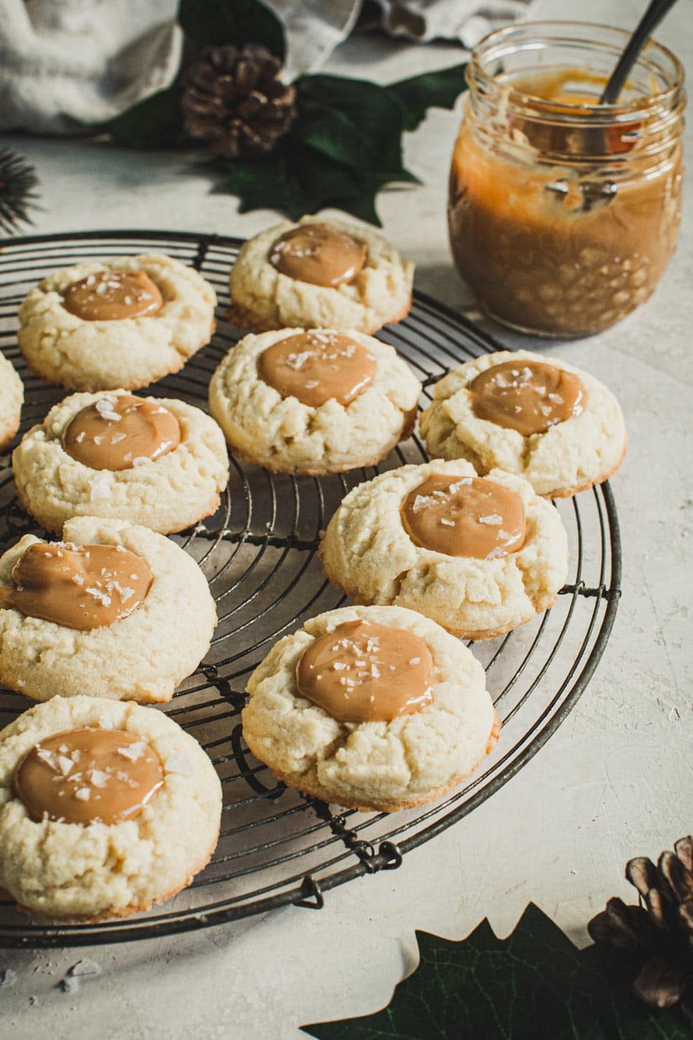 Dulce de Leche Thumbprint cookies on a round wire rack with sauce in a jar behind them.