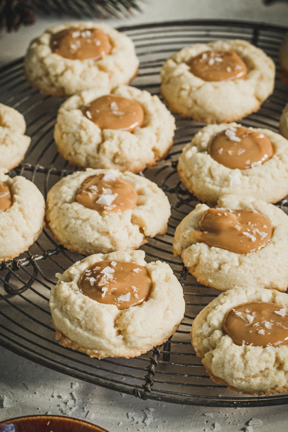 Close up of thumbprint cookies topped with dulce de Leche and salt flakes.
