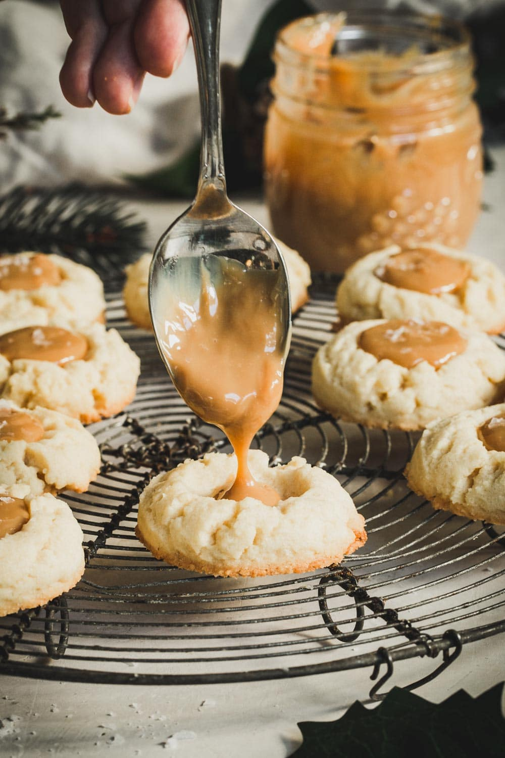 Silver spoon dropping Dulce de Leche into a baked thumbprint cookie.