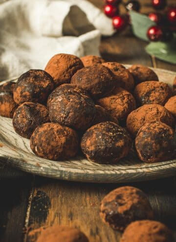Chocolate rum balls stacked on a wooden plate.