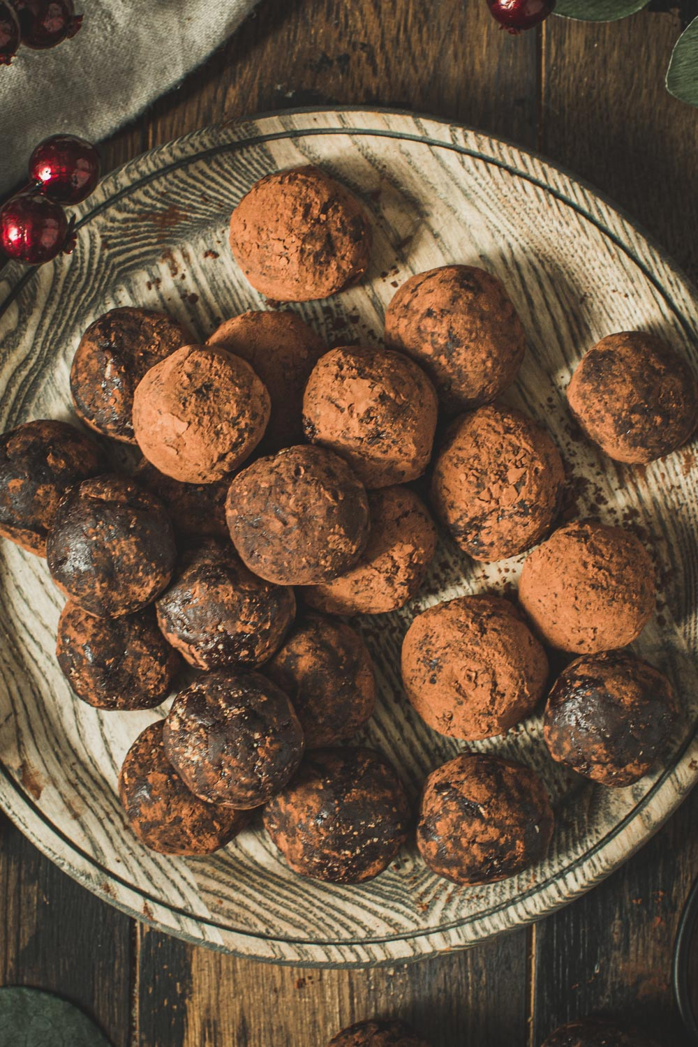 Rum balls coated in cocoa powder on a wooden plate.