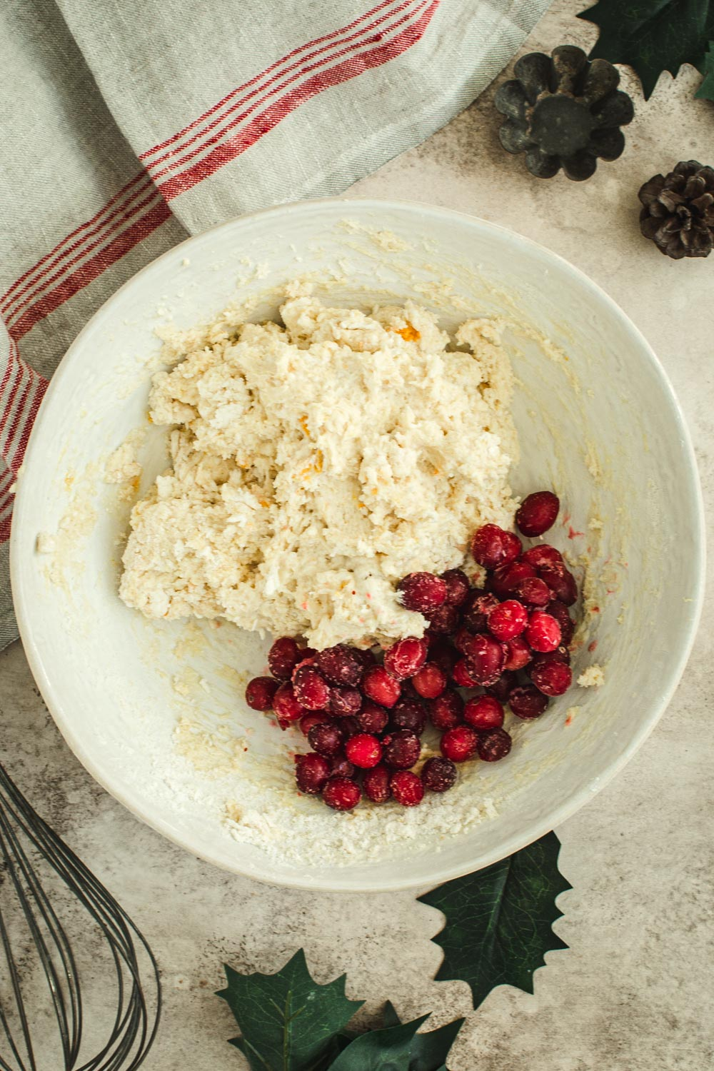 Scone dough with cranberries in white bowl.