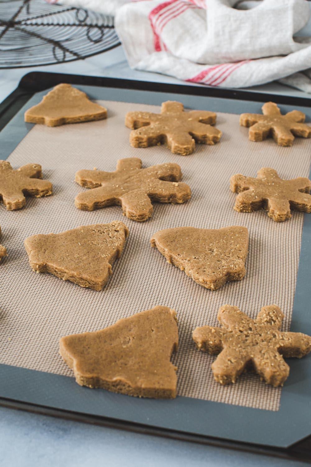 Gingerbread cookie dough cutouts on a baking sheet.