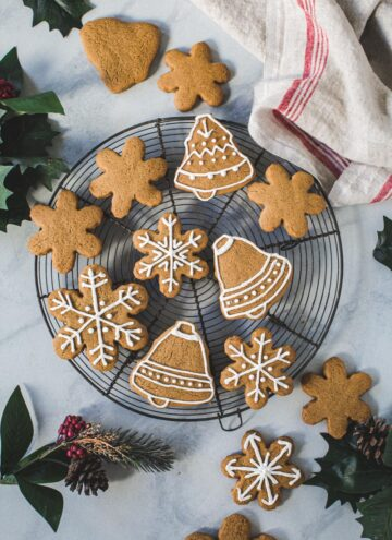Gingerbread cookies with royal icing on a round wire baking rack.