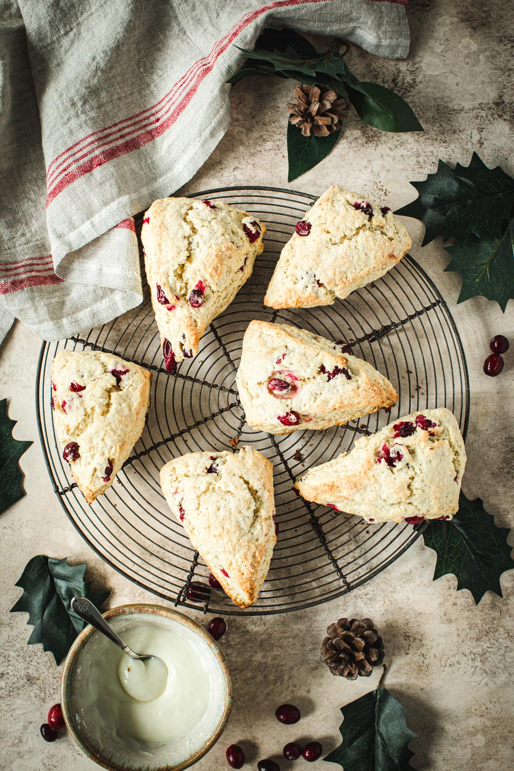 Cranberry Orange Scones on a wire rack with a red and white dish towel next to it.