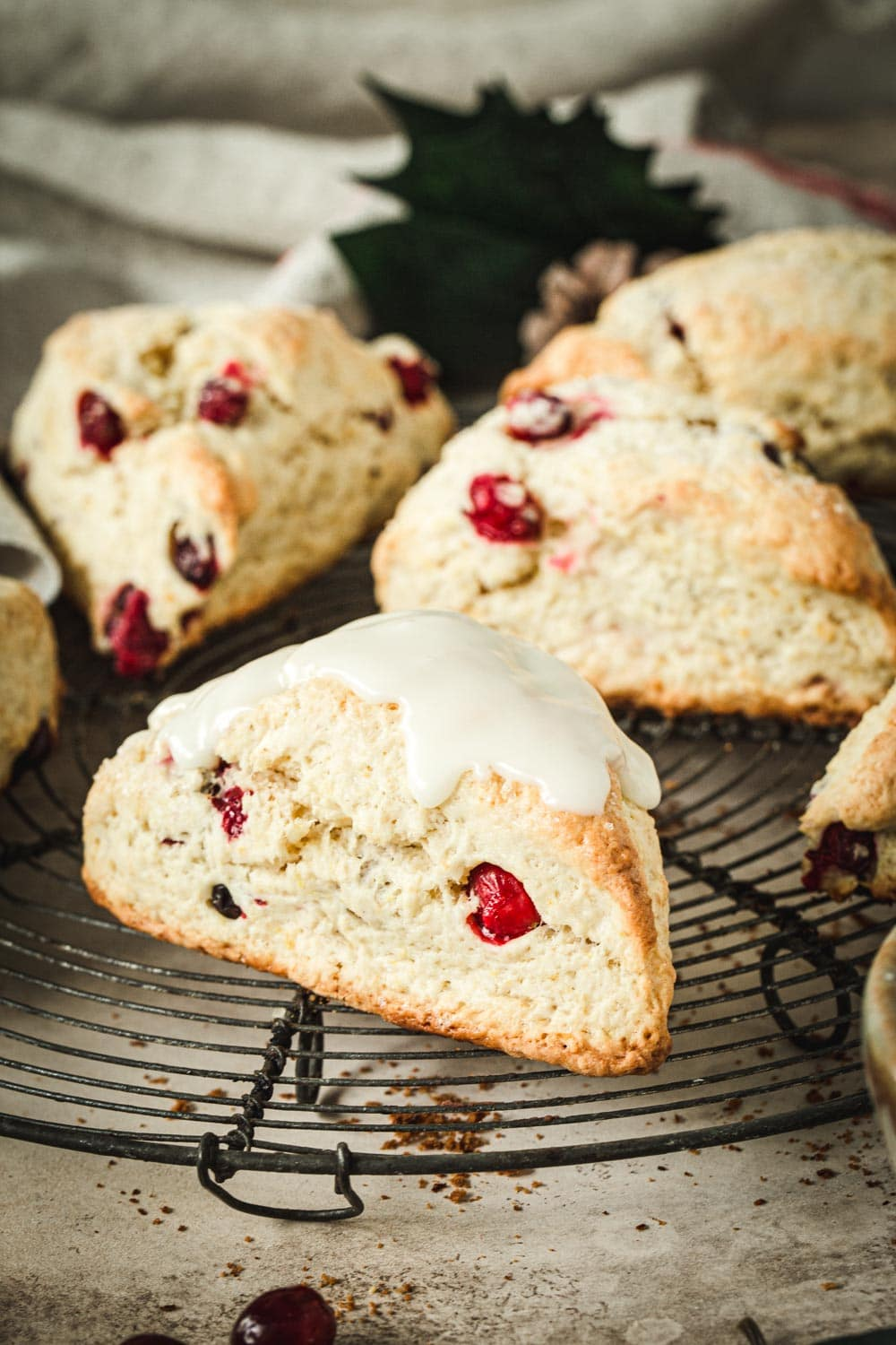 Cranberry orange scones covered in icing sitting on a wire rack.
