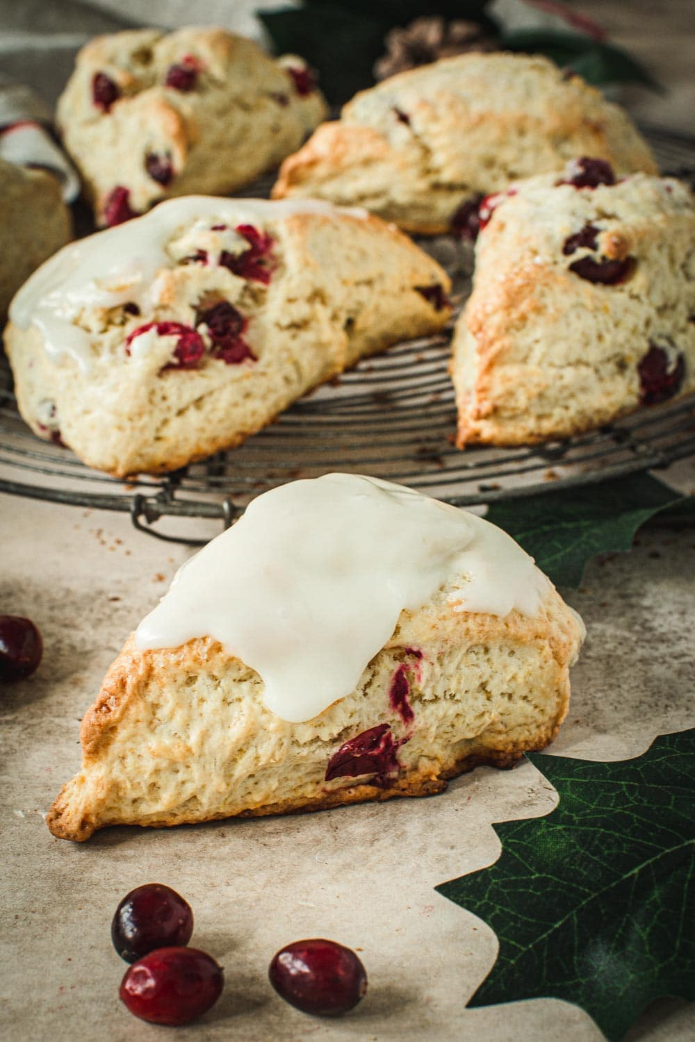 Cranberry orange scone covered in an orange glaze with scones behind it on a wire rack.
