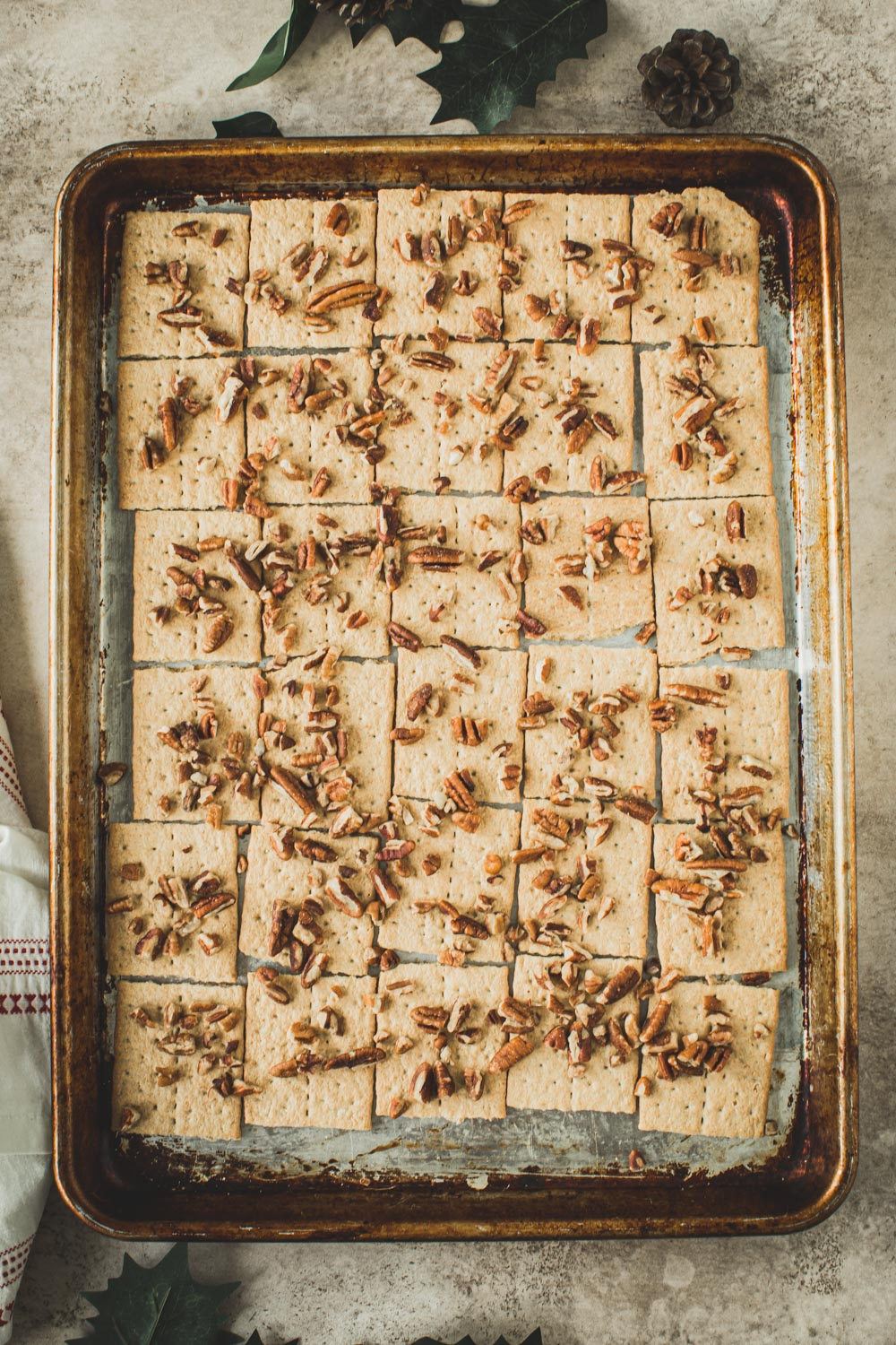 Graham Crackers covered in pecans on a rimmed baking sheet.