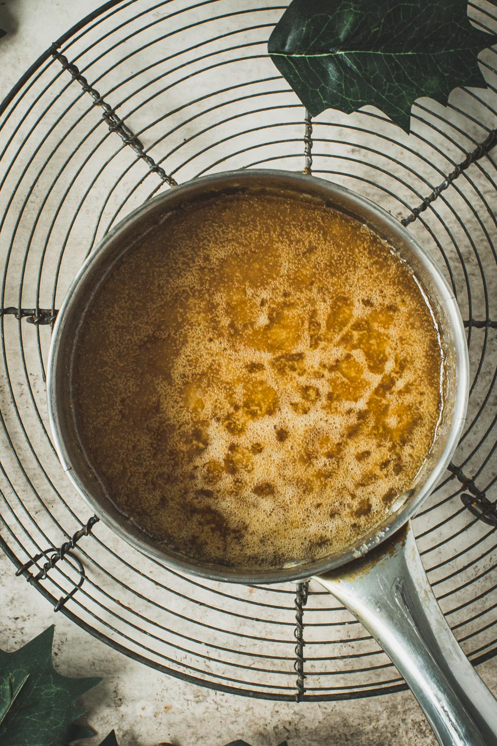 Boiling caramel for praline bars in a small pot.