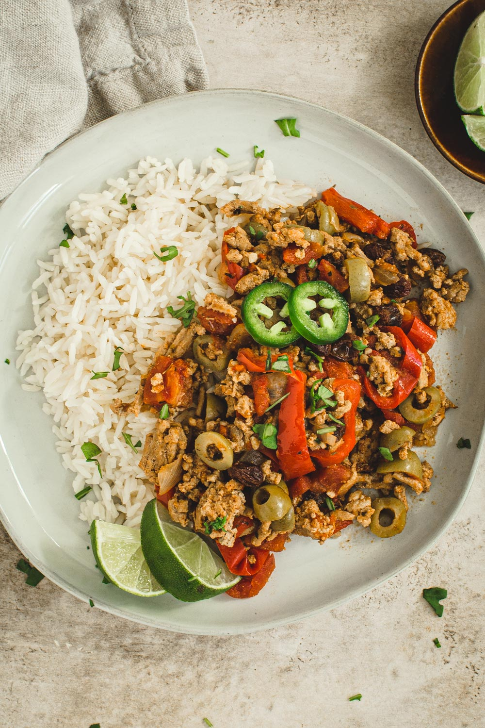 Instant pot picadillo topped with cilantro and lime wedges over rice.
