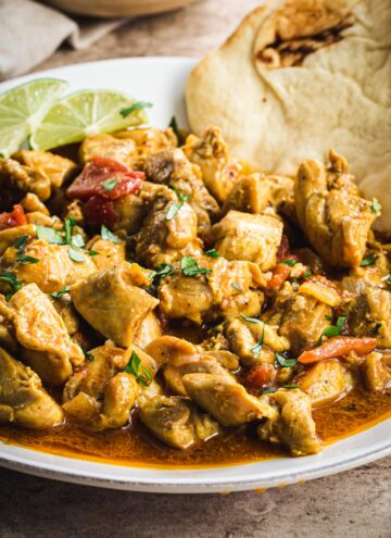 Creamy coconut chicken curry close up garnished with cilantro and lime wedges.
