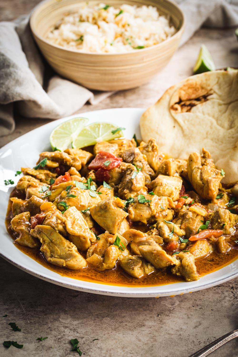 Creamy coconut chicken curry on a white plate with Naan and lime wedges.