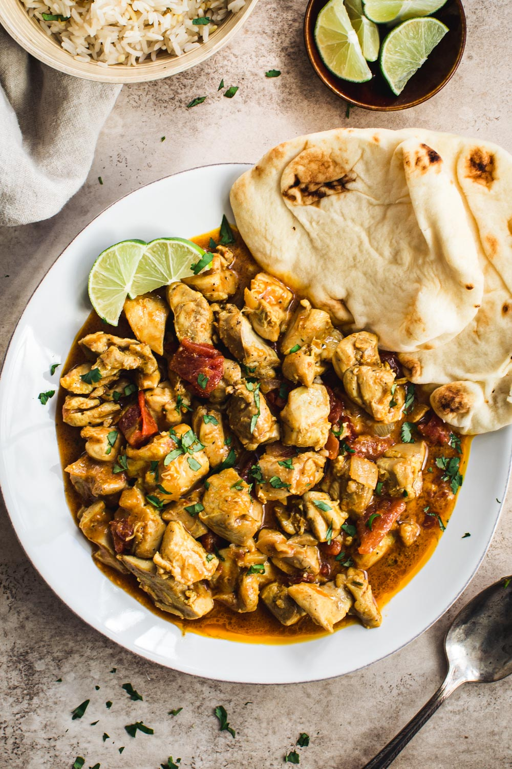 Creamy coconut chicken curry with Naan and lime wedges on a white plate.