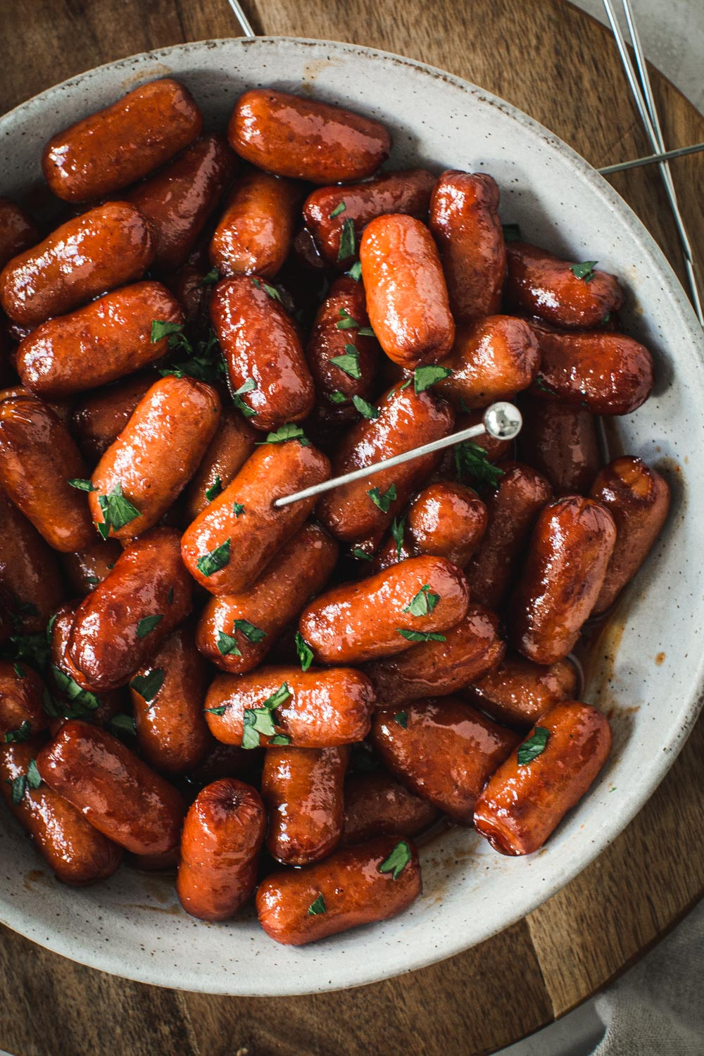 Honey sriracha Little Smokies topped with chopped cilantro in a white bowl.