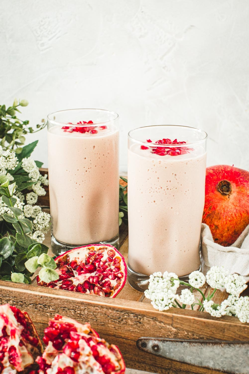 Pomegranate mango smoothies in glass cups with pomegranate seeds on top.