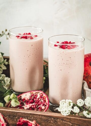 Two pomegranate mango smoothies topped with pomegranate seeds.