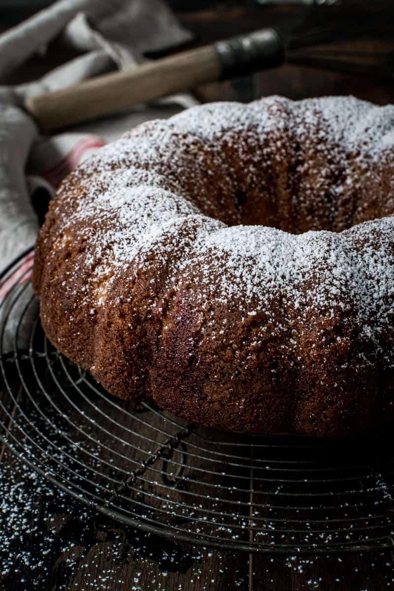 Red velvet marble bundt cake coated in powdered sugar.