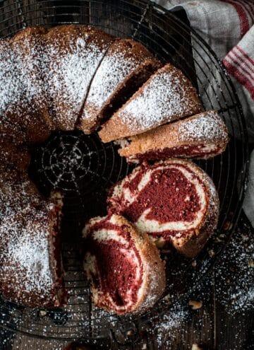 Red velvet marble bundt cake sliced and covered in powdered sugar.