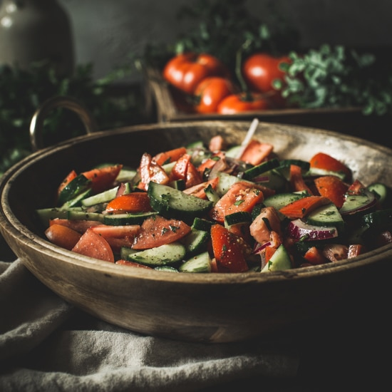 Cucumber tomato salad in a wooden bowl sitting on a cream towel.