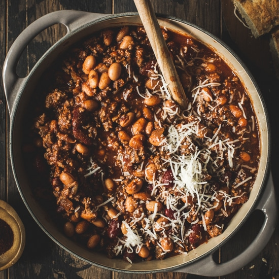 Game day chili topped with cheese in a large gray Dutch oven/
