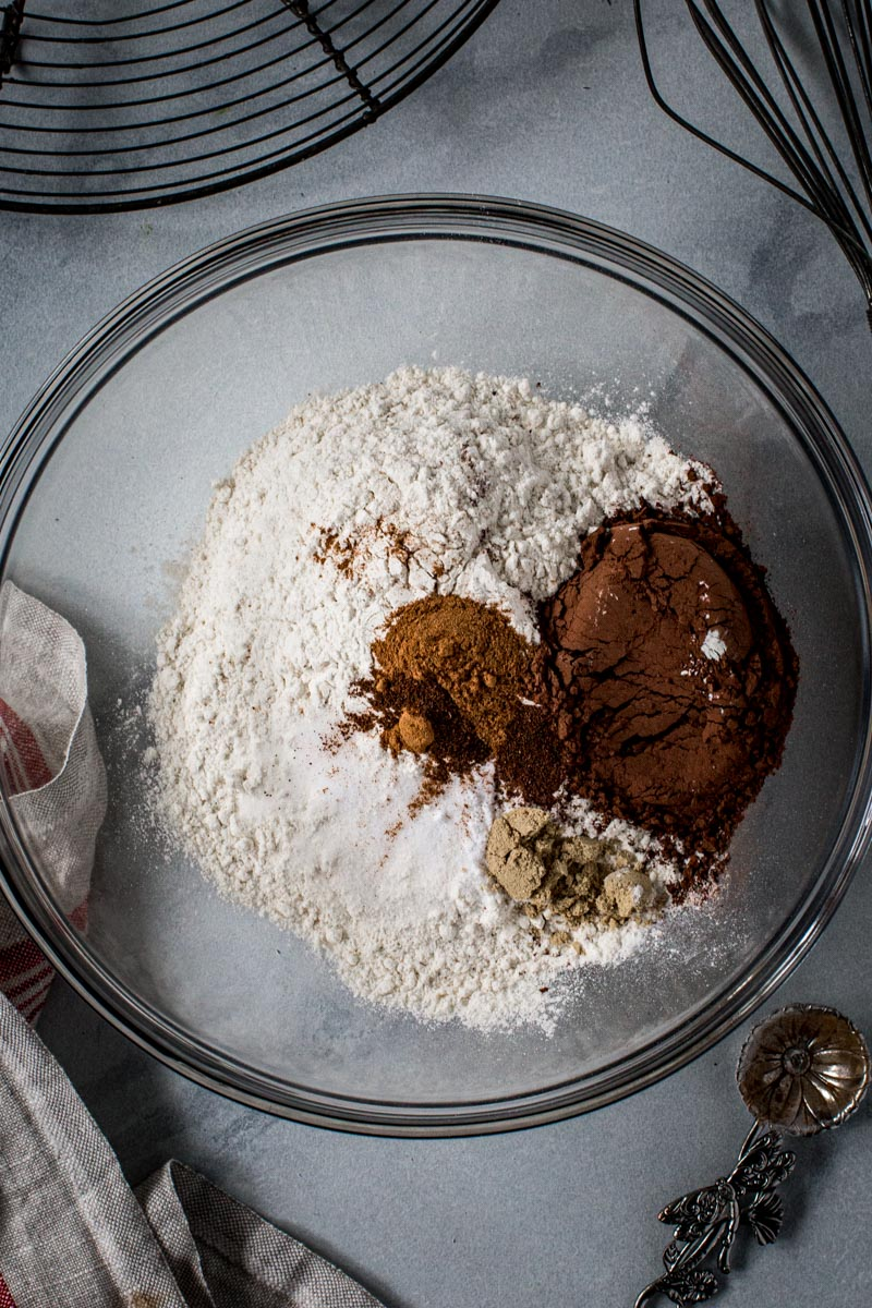 Dry ingredients for soft ginger cookies in a glass mixing bowl.