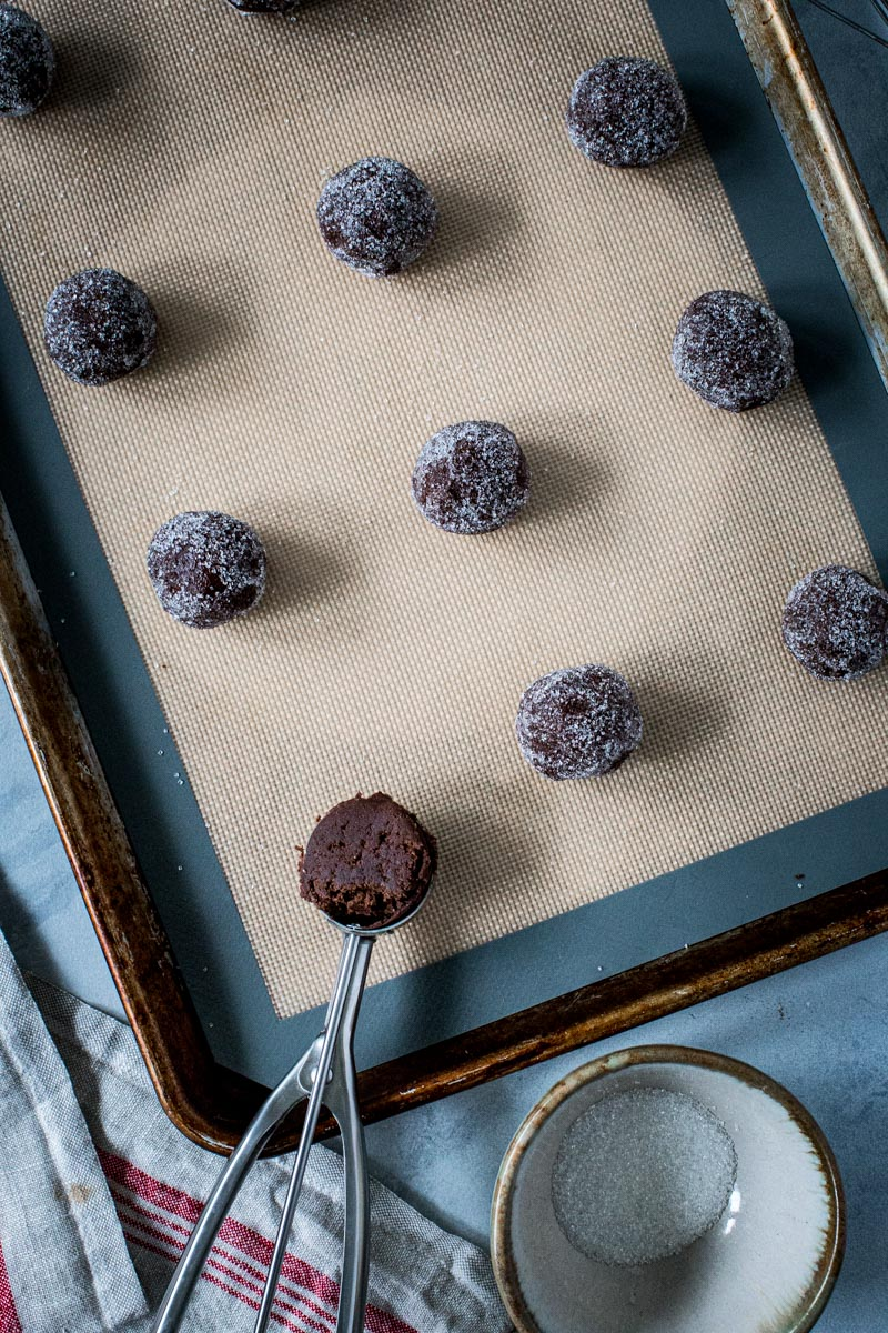 Ginger cookie dough balls rolled in sugar on a baking sheet.