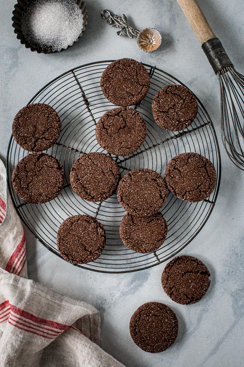 Chocolate ginger cookies on a round wire rack with red and cream towel next to it.