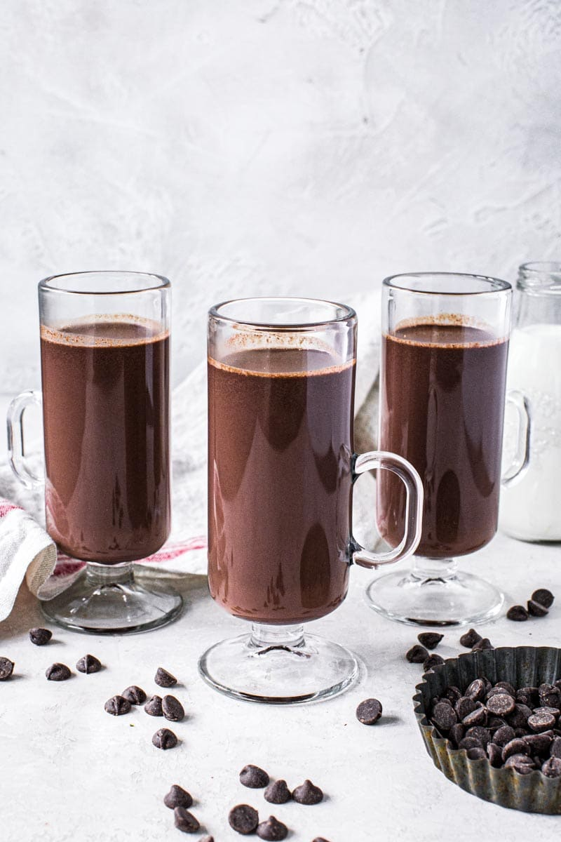 Three hot chocolates in tall glasses with slim handle.