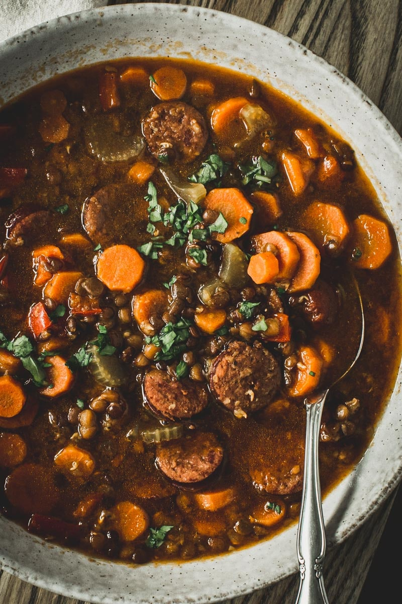 Silver spoon in sausage and lentil stew in a white bowl.