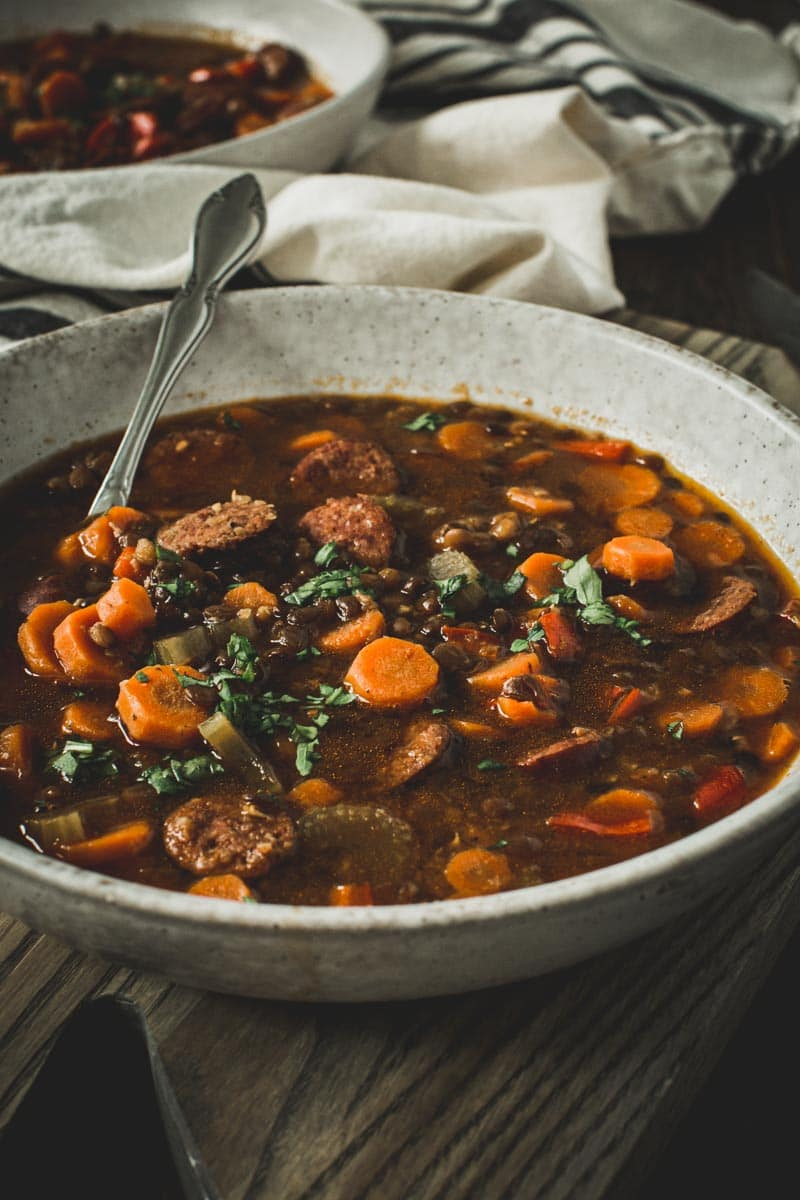 Sausage and lentil stew with a silver spoon in a white bowl.
