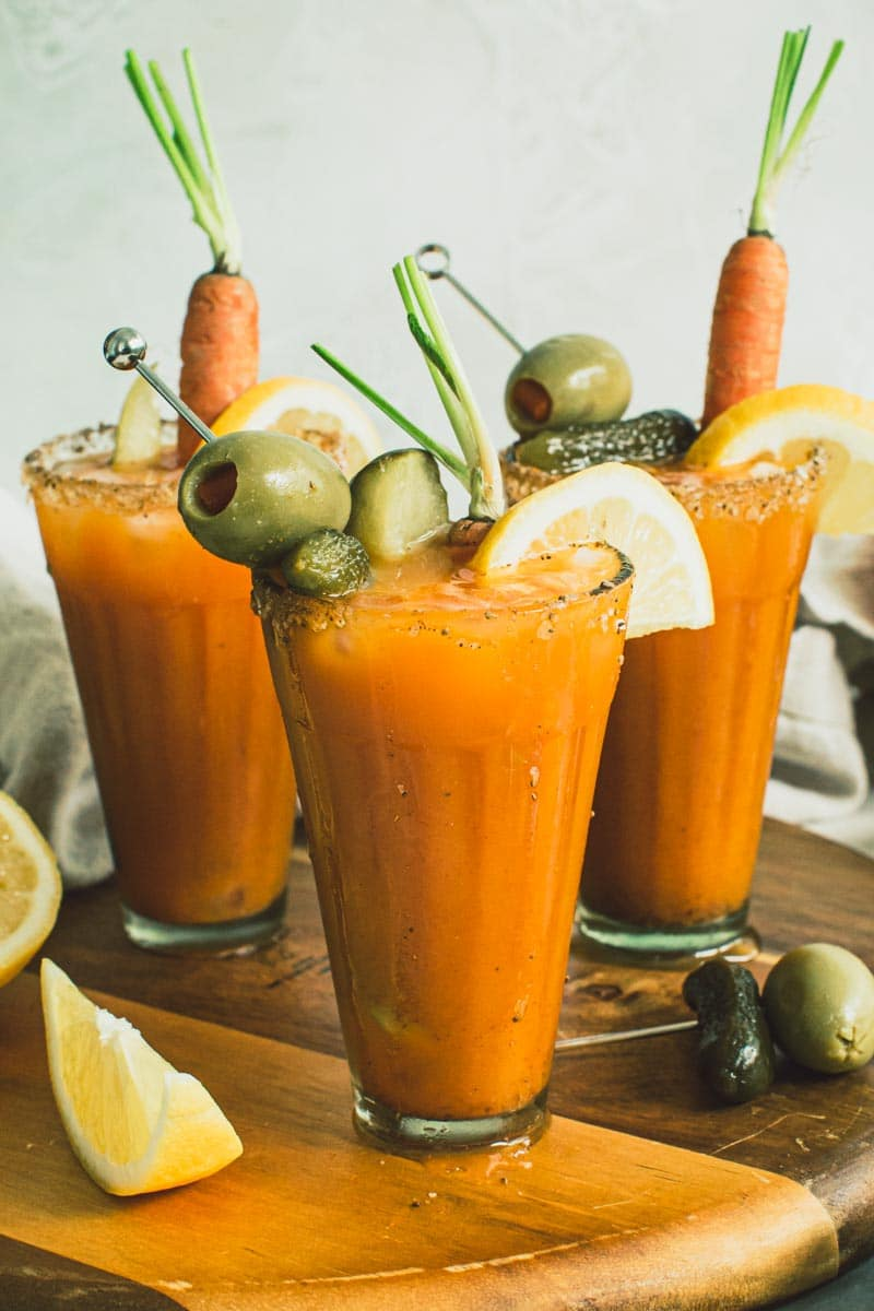 Bunny Mary cocktails in small glasses topped with carrots, lemon slices, and olives.