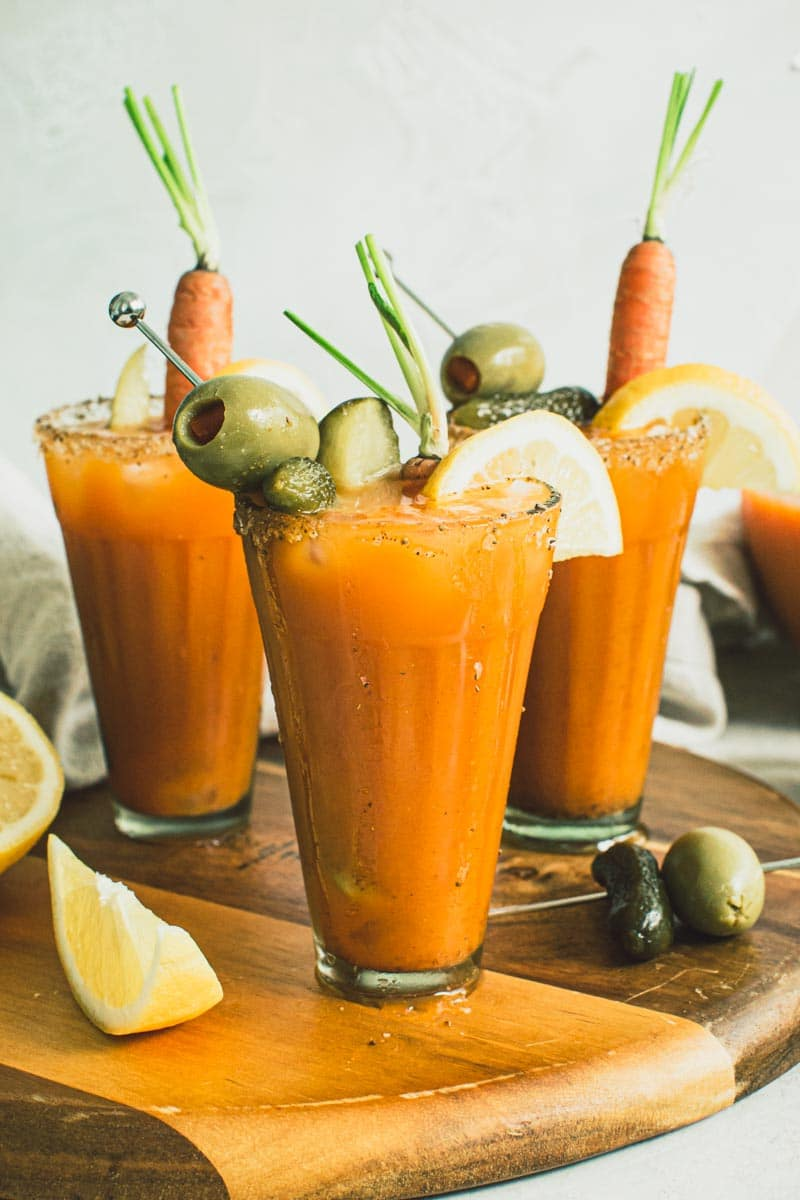 Carrot Juice Bloody Mary cocktails in glasses topped with garnishes and sitting on a wooden board.